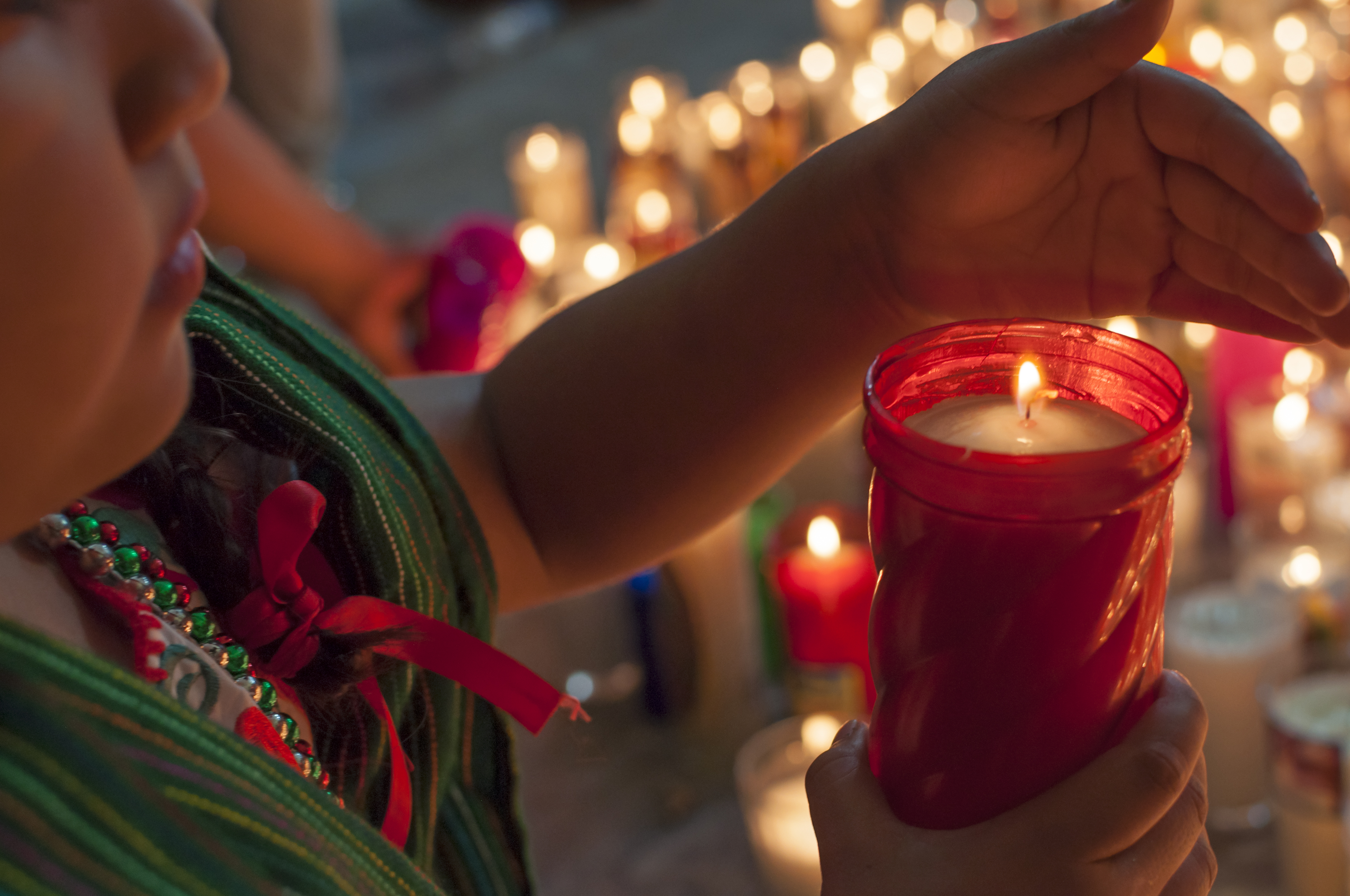 Our lady of Guadalupe girl lights candle after mass iStock-530098565